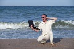 Sonnenverbrannter Mann mit Telefon und Laptop Stockfotografie