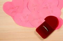 Sonnez dans la boîte sur le tas des coeurs de papier Image stock