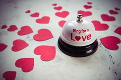 Sonnez la cloche pour un amour et beaucoup de coeurs sur un fond en bois Photographie stock libre de droits