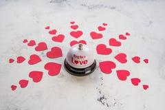 Sonnez la cloche pour un amour et beaucoup de coeurs sur un fond en bois Images stock