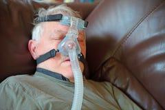 Sonni dell'uomo più anziano che indossano il dispositivo di CPAP immagini stock libere da diritti