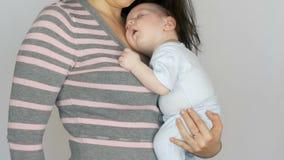 Sonni di due mesi divertenti del neonato in armi di sua madre La mamma oscilla suo figlio del bambino archivi video