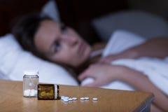 Sonniferi in pillole che si trovano sul comodino Immagini Stock Libere da Diritti