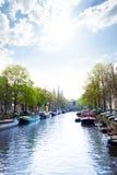 Sonnige Ansicht von Amsterdam auf dem Fluss und den Booten Stockfotos
