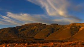 Sonnige Berge Wolken durchgebrannt durch den Wind über dem Gipfel Blauer Himmel lizenzfreie stockbilder