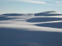Sonnige Dünen von frisch schneien Stockfoto