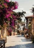 Sonnige gehende Straße mit blühenden purpurroten Blumen in historischer Mitte Antalyas - Kaleici, die Türkei lizenzfreie stockbilder