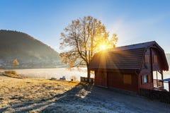Sonnige Herbstlandschaft, Holzhaus am alpinen See Lizenzfreies Stockfoto