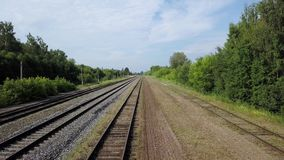 Sonnige Landschaft von den leeren langen Eisenbahnen, die nach Grüner Grenze von Büschen und von Bäumen legen stock footage