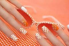 Sonnige orange Maniküre mit Punkten stockbild