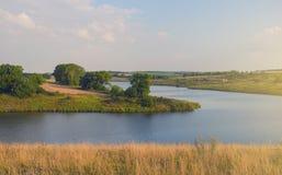 Sonnige Sommerlandschaft mit Fluss, Feldern, grünen Hügeln und schönen Bäumen lizenzfreie stockfotos