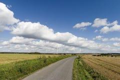 Sonnige Windmühle und eine Straße Stockbilder