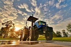 Sonniger, blauer Himmel und weiße Wolken des guten Wetters, ein Traktor Lizenzfreies Stockfoto