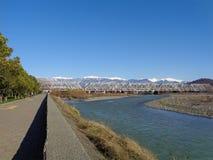 Sonniger Flussdamm, Eisenbahnbrücke und Schnee-mit einer Kappe bedeckte Berge auf dem Horizont Stockfoto