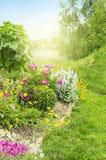 Sonniger Garten mit Blumenbeet Stockfotos