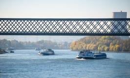 Sonniger Herbsttag in Deutschland auf dem Fluss Rhein Der Lastkahn fließt unter die Eisenbahnbrücke Ein sichtbarer Kamin eines Ke lizenzfreie stockfotos