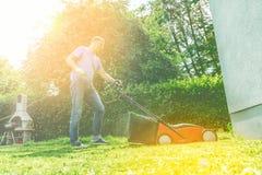Sonniger Rasen des Sommers und der Frühlings-Saison, der im Garten mäht stockfoto