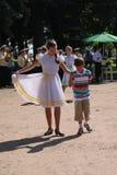 Sonniger Sommertag im Stadtpark allgemeine Entertainer der Mädchen, die mit den Touristenleuten unter die Musik eines Militärmess Lizenzfreies Stockfoto