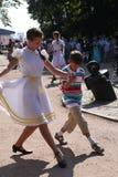 Sonniger Sommertag im Stadtpark allgemeine Entertainer der Mädchen, die mit den Touristenleuten unter die Musik eines Militärmess Lizenzfreie Stockfotografie
