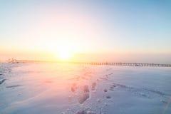 Sonniger Sonnenaufgang über der schneebedeckten Ebene Stockbild
