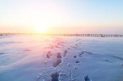 Sonniger Sonnenaufgang über der schneebedeckten Ebene Stockbilder