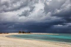 Sonniger Strand, dunkle Wolken und Türkis wässern Paradies-Insel, Bahamas Lizenzfreie Stockfotos