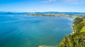 Sonniger Strand mit Ackerland auf dem Hintergrund Auckland, Neuseeland Stockfotografie