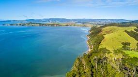 Sonniger Strand mit Ackerland auf dem Hintergrund Auckland, Neuseeland Lizenzfreie Stockbilder