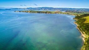Sonniger Strand mit Ackerland auf dem Hintergrund Auckland, Neuseeland Stockfotos