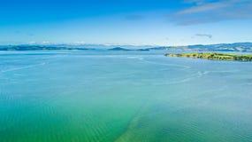 Sonniger Strand mit Ackerland auf dem Hintergrund Auckland, Neuseeland Lizenzfreies Stockfoto