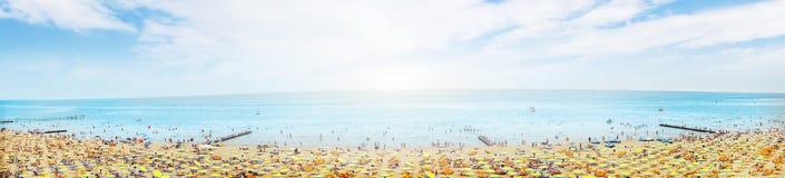 Sonniger Strand mit Sonnenschutz auf blauem bewölktem Himmel Lizenzfreies Stockfoto