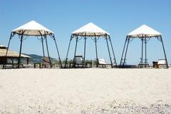 Sonniger Strand mit 3 Zelten Lizenzfreies Stockfoto