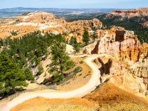 Sonniger Tag in Bryce Canyon, Utah, USA Staubige Landstraße im felsigen Tal mit grünen Bäumen Stockfotos
