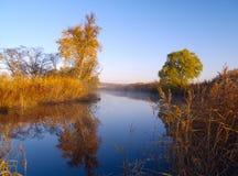 Sonniger Tag des Herbstes in hölzernem See Stockbild