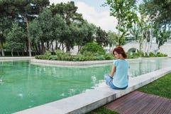 Sonniger Tag des Sommers Junge Frau sitzt draußen auf Küste des Kanals Mädchen, das nach Training stillsteht Stockfotografie