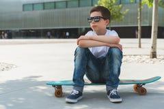 Sonniger Tag des Sommers Junge in weißem T-Shirt und Sonnenbrillesitzen im Freien auf longboard Jungenreste nachdem dem Ski fahre lizenzfreies stockbild