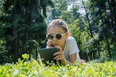 Sonniger Tag des Sommers nettes Mädchen in der Sonnenbrille, die auf grünem Rasen mit ihrem Gerät liegt Mädchen, das auf Gras sti stockfoto