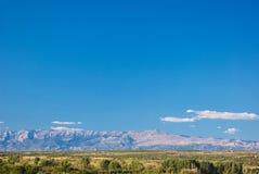 Sonniger Tageslandschaft des kroatischen grünen Feldes, der Berge und des blauen Himmels Lizenzfreies Stockfoto