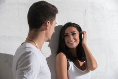 Sonniges Foto der jungen Paare gegen weiße Wand Lizenzfreies Stockbild