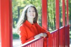 Sonniges Porträt der jungen Frau orange Mantel am Achterbahnparkhintergrund tragend stockfotos