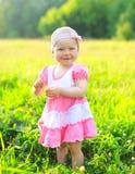 Sonniges Porträt des lächelnden Kindes auf dem Gras im Sommer Stockfotografie