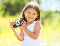 Sonniges Porträt des netten lächelnden Kindes des kleinen Mädchens mit alter Kamera Lizenzfreies Stockfoto