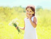 Sonniges Porträt des netten lächelnden Kindes des kleinen Mädchens mit Blumen Lizenzfreie Stockfotos