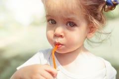 Sonniges Porträt eines kleinen Kindes, das von einem Stroh juiceon trinkt, verwischte Sommerhintergrund lizenzfreie stockfotos