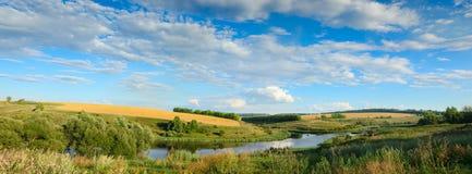 Sonniges Sommerpanorama mit Fluss, goldenen Weizenfeldern, grünen Hügeln und schönen flaumigen Wolken im blauen Himmel bei Sonnen stockfoto