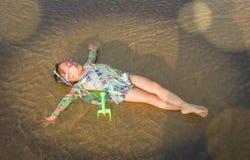Sonno asiatico del bambino sul sole del mare della sabbia Immagini Stock Libere da Diritti