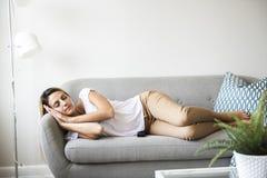 Sonno biondo delle donne sul sofà a casa immagine stock libera da diritti