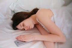 Sonno castana della giovane donna a letto Telefono cellulare vicino lei Fotografia Stock Libera da Diritti