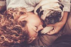 Sonno caucasico piacevole di signora sul sofà con i suoi due cani dei carlini che la proteggono Immagini Stock Libere da Diritti
