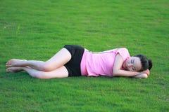 Sonno cinese asiatico felice della donna su erba Immagine Stock